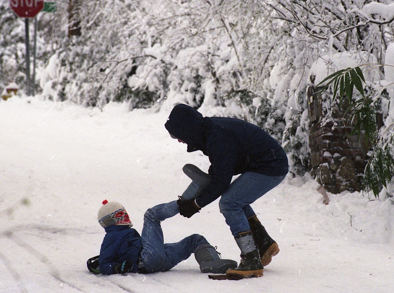 Bruce Anderson helps his 7-year-old son James get his boot back on in March 1993. James' boot filled with snow while he was sledding with his father and neighbors in the Sequoyah Hills area of Knoxville.