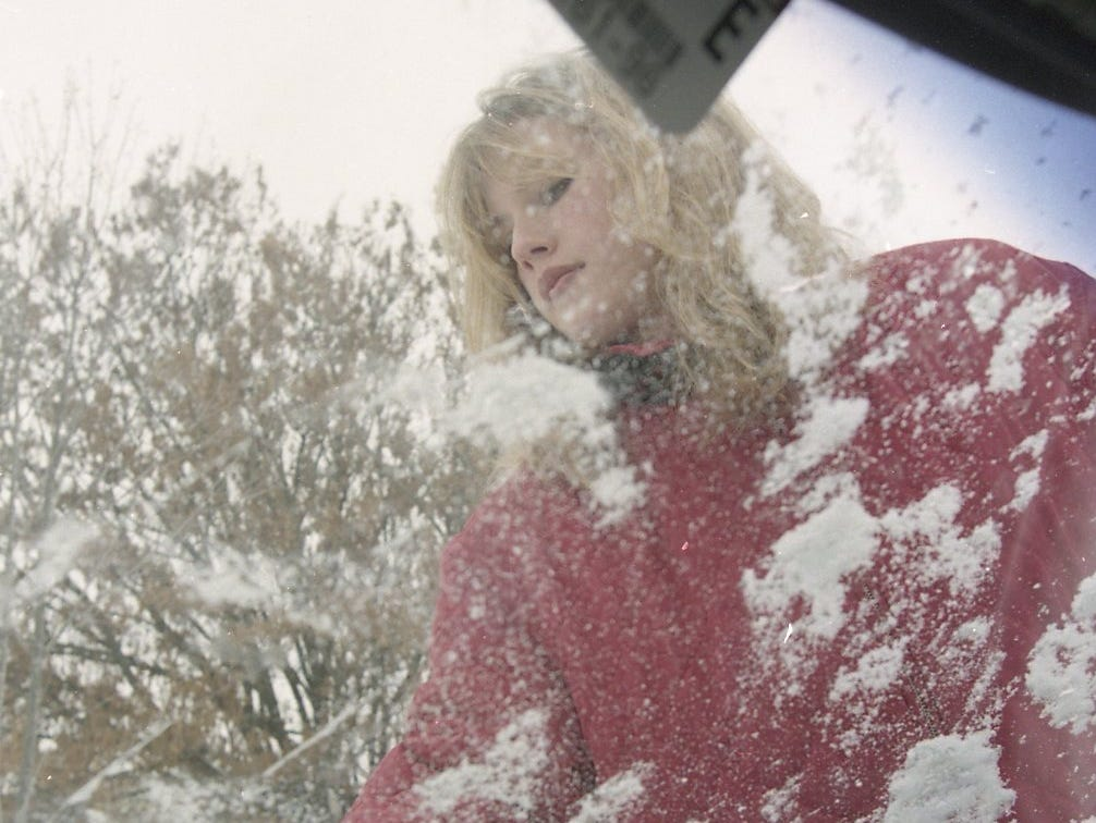 "Rel Ann Fortner tries to clear the windshield of her car, which has been covered in snow since last Wednesday in February 1996. ""My hands are freezing,"" Fortner said, who is a UT student and has been stuck on campus since last week's snow storm hit."