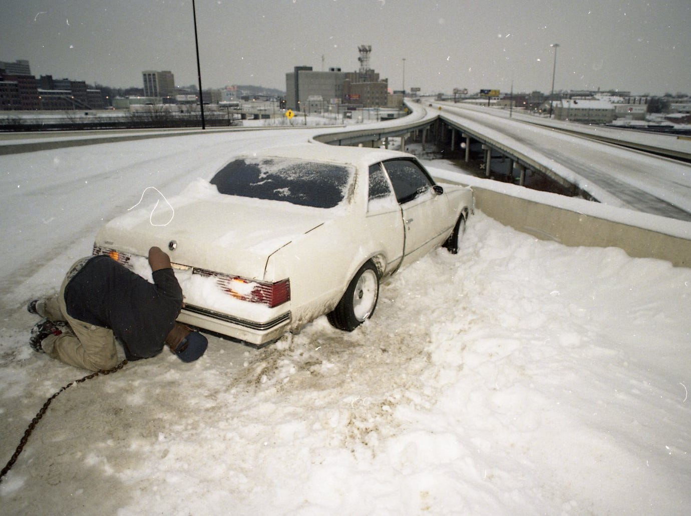 William Houston of Knoxville works to attach a chain to his car after sliding on to the shoulder and getting stuck in February 1996 on the access ramp from I-275 to I-40 East.