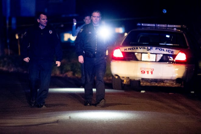 Knoxville police officers walk at the scene of a shooting near Speedway Circle and Calvin Street in Knoxville, Tennessee on Sunday, November 11, 2018.