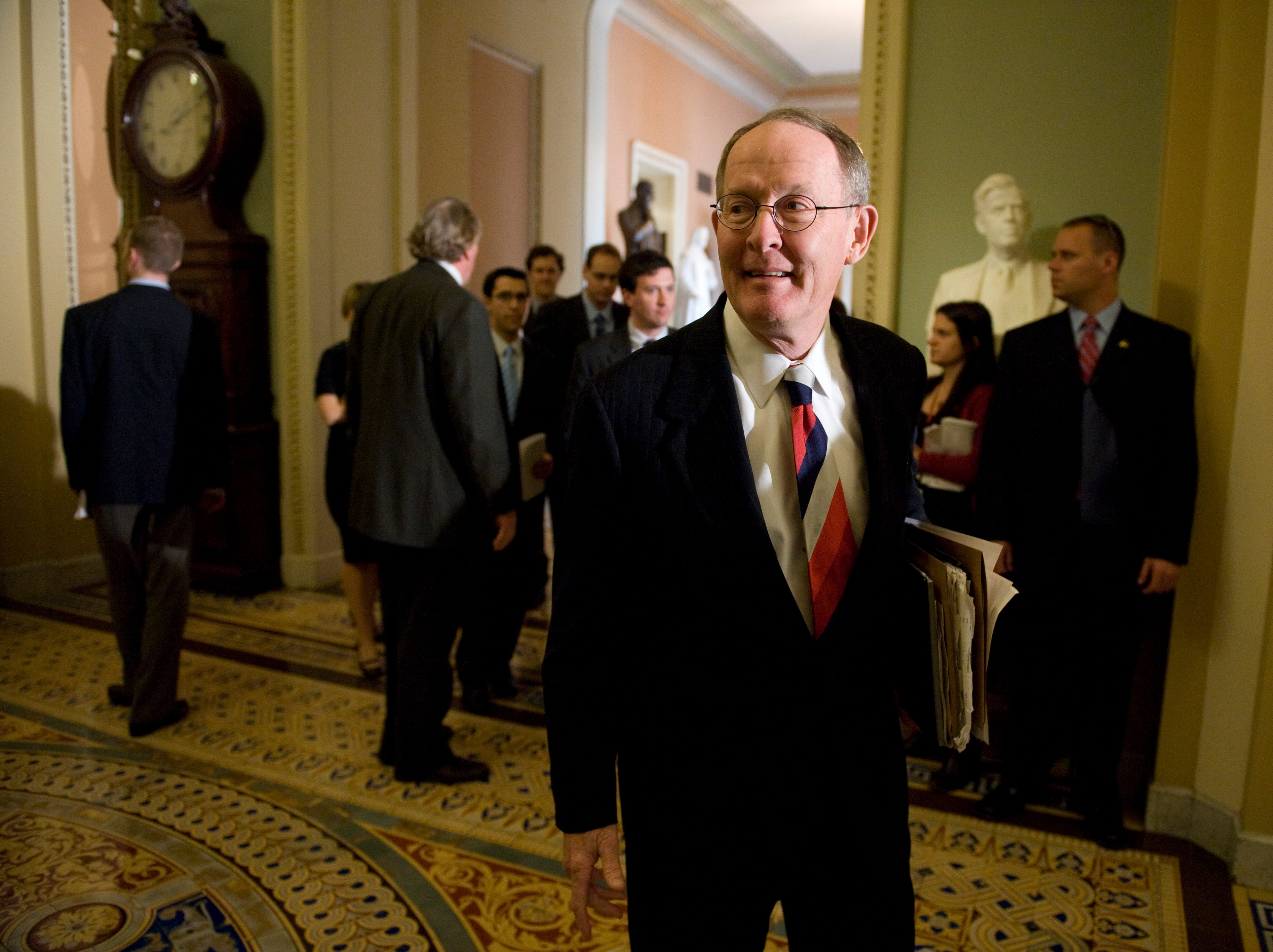 Sen. Lamar Alexander, R-Tenn., walks through the Ohio Clock Corridor in the U.S. Capitol on his way to join the other Senate Republican leaders for their weekly news conference following the Senate Republican Policy Luncheon on Tuesday, May 20, 2008. Sen. Alexander's chief of staff Tom Ingram is seen in the background to the left.