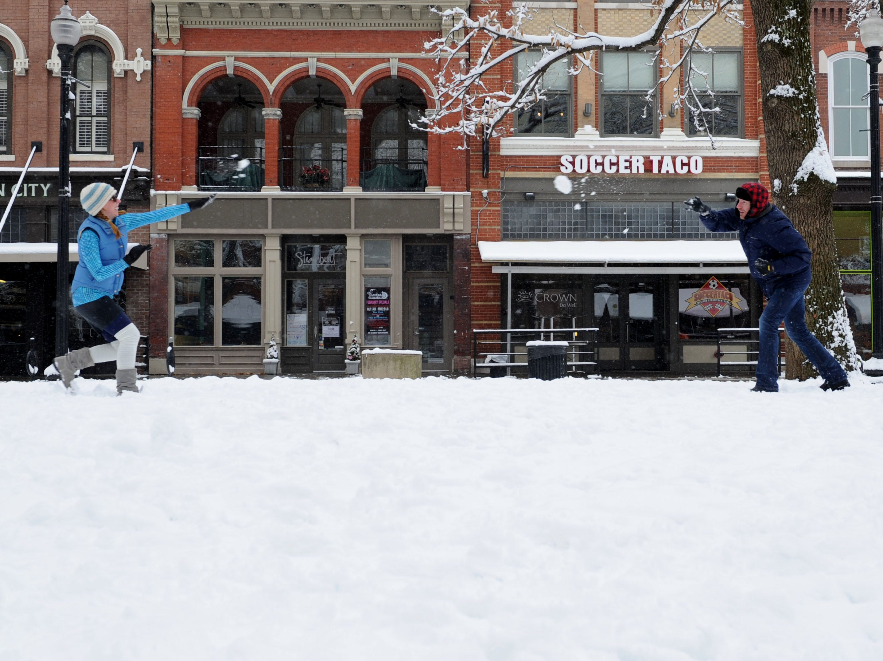 Morgan Fleming, left, and Jamie Shoemaker have a snowball fight at Market Square in downtown Knoxville on Thursday, Feb. 13, 2014. The winter storm on Wednesday brought six inches of snow to the Knoxville area.
