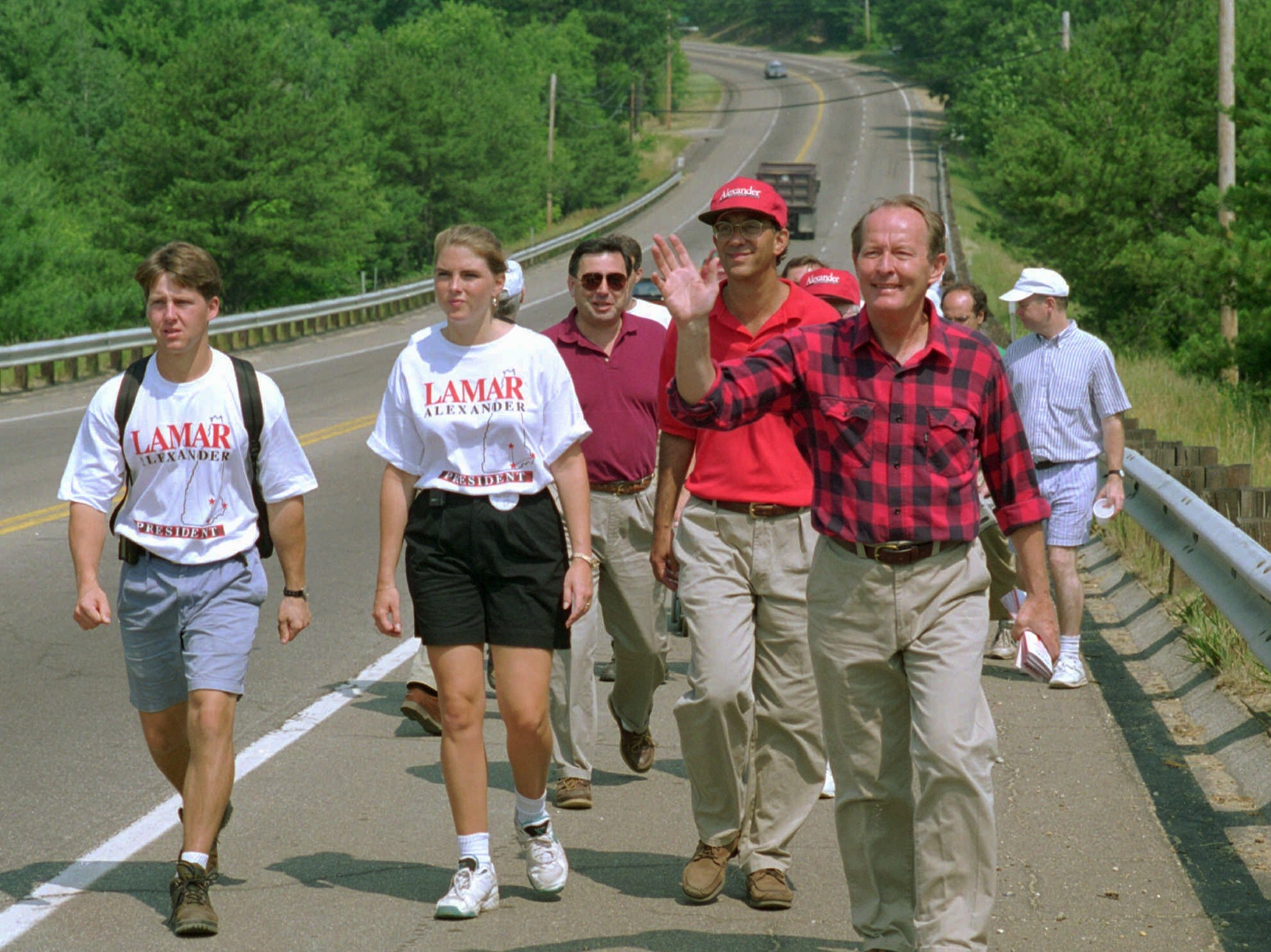 Republican presidential hopeful and former governor of Tennessee, Lamar Alexander, in the checkered shirt, waves to cars during the start of Alexander's 90 mile walk across the state in Concord, N.H., Thursday, July 6, 1995.  Alexander is hoping to pickup votes the old fashioned way.