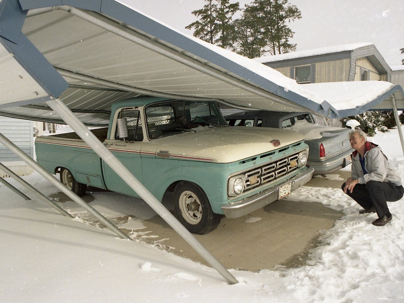 Lester Haring of Clayton Estates looks at the damage to his 1963 Ford pickup and his 1993 Chrysler New Yorker after snow caused his carport to collapse in February 1996. Haring said the structure was only five months old.