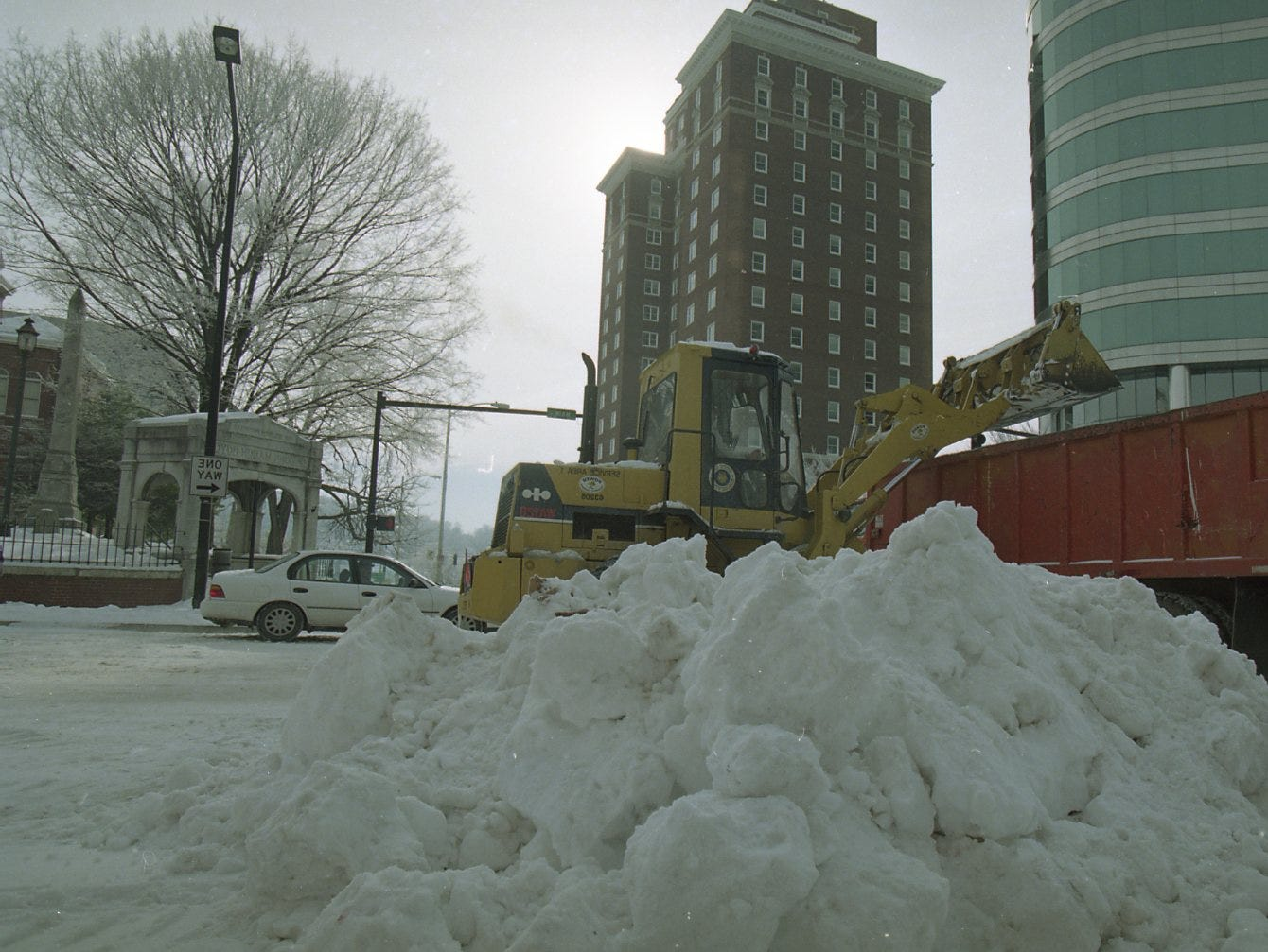 City street crews use a front end loader to remove large piles of plowed snow from the corner of Gay St. and Main St. in downtown Knoxville in February 1996.