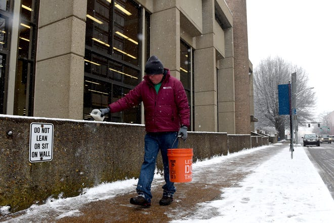 A Knox County employee spreads salt in front of the Lawson McGhee Library during snowfall in downtown Knoxville on Feb. 12, 2016.