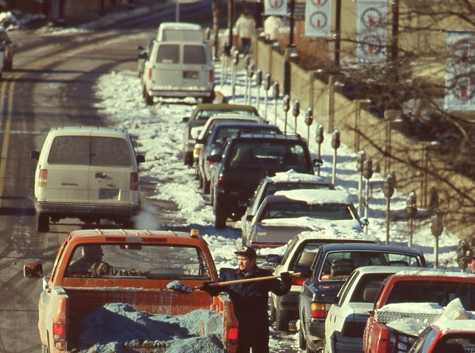 Public service worker WIllie Long throws salt on the sidewalks along Church St. in January 1996.