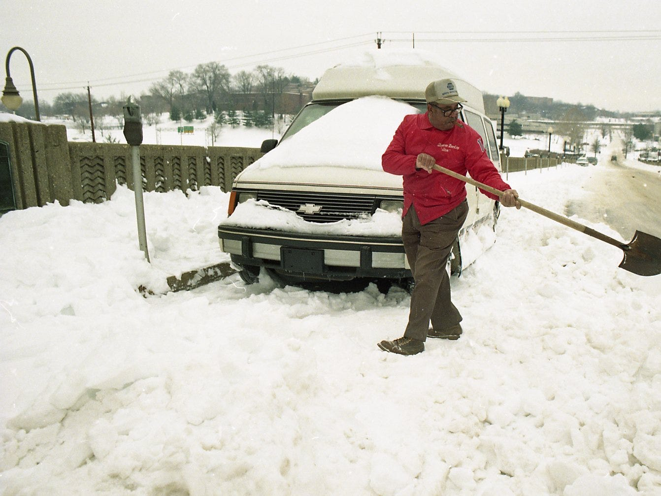 Abe Burton of Knoxville digs snow from around a mini-van parked on the Church Avenue viaduct in February 1996. Although the van doesn't belong to Burton, he said he had dug out his own car on the bridge and thought he would help the owner of the van.