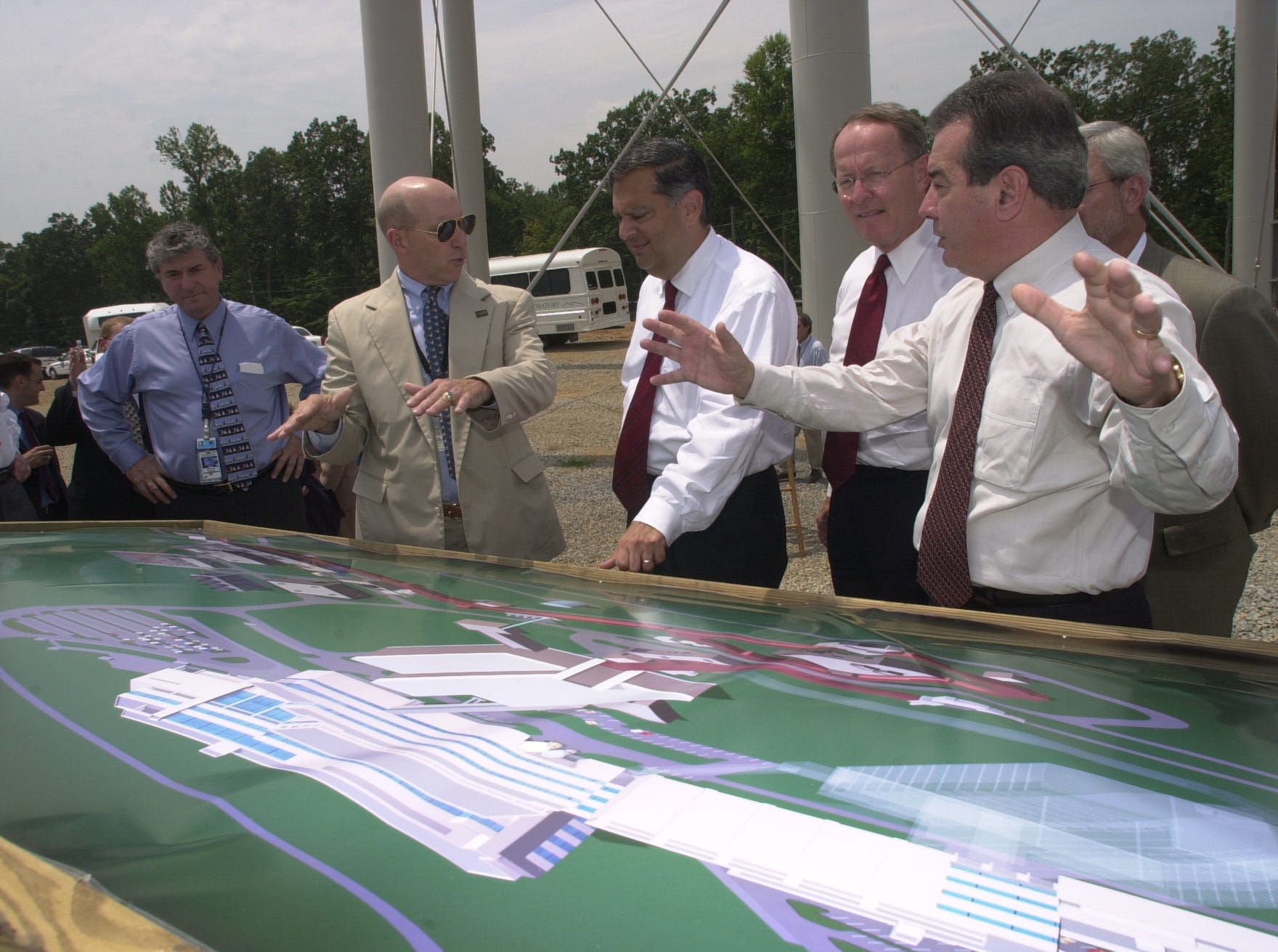 ORNL Director Bill Madia, right, gives an overview of the Spallation Neutron Source project to U.S. Energy Secretary Spencer Abraham, second from left, and Sen. Lamar Alexander Friday at the Oak Ridge National Laboratory. At left is SNS Deputy Project Director Carl Strawbridge. Abraham and Alexander attended a groundbreaking ceremony for the $65 million Center for Nanophase Materials Sciences.