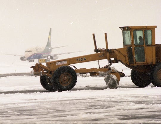An AirTran flight from Orlando taxis into McGhee Tyson Airport's terminal as a road grader tries to clear snow from the taxi way.