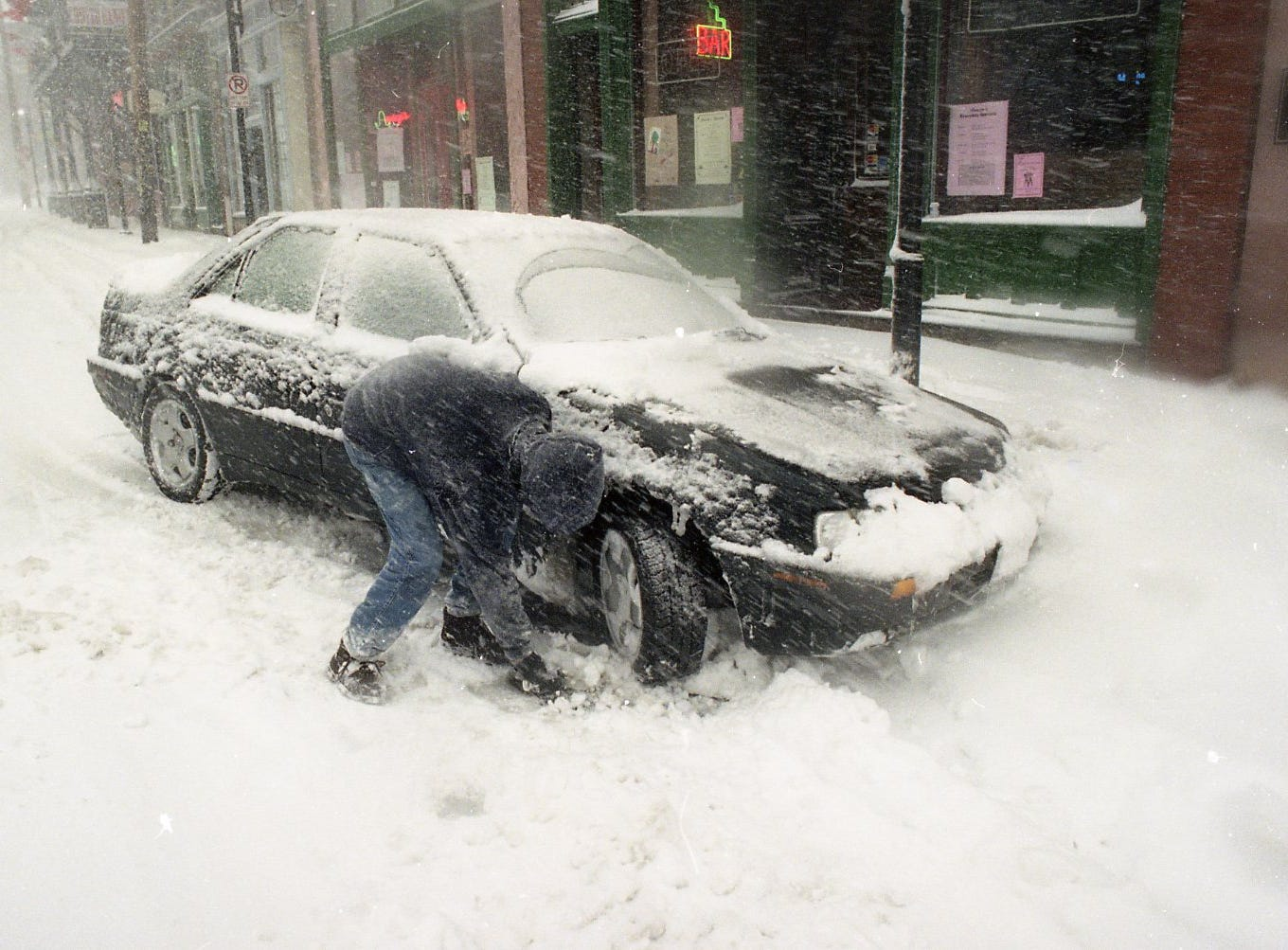 Robert Escarcega, a UT student, uses a dust pan to clear snow from the front of his tires as the snow falls sideways down Central St. in the Old City in March 1993.
