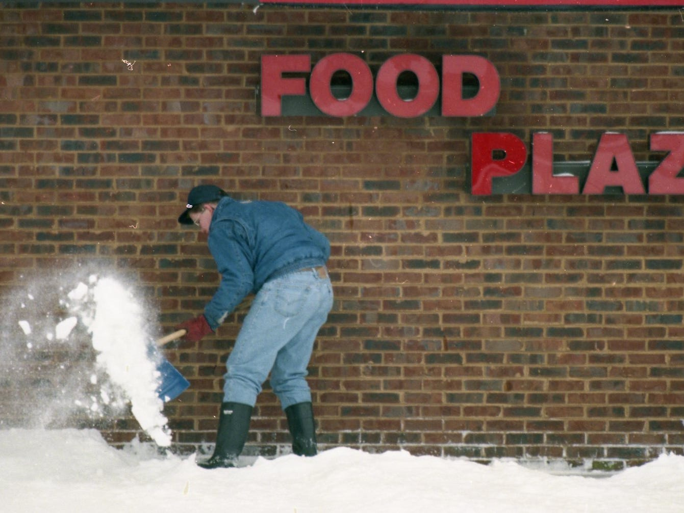 A man works to clear the parking lots of the Phillips 66 station at the intersection of Kingston Pike and Peters Road in February 1996.