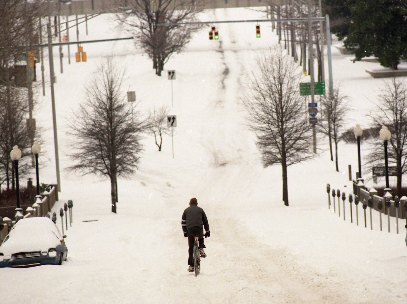 Al Brooks, who had the day off from his job, peddles his bike into a snowy landscapes on Church Ave. in February 1996. Brooks is a veteran of many winters in his hometown of Rockford, Ill., and expressed amazement that snow would close down on Knoxville.