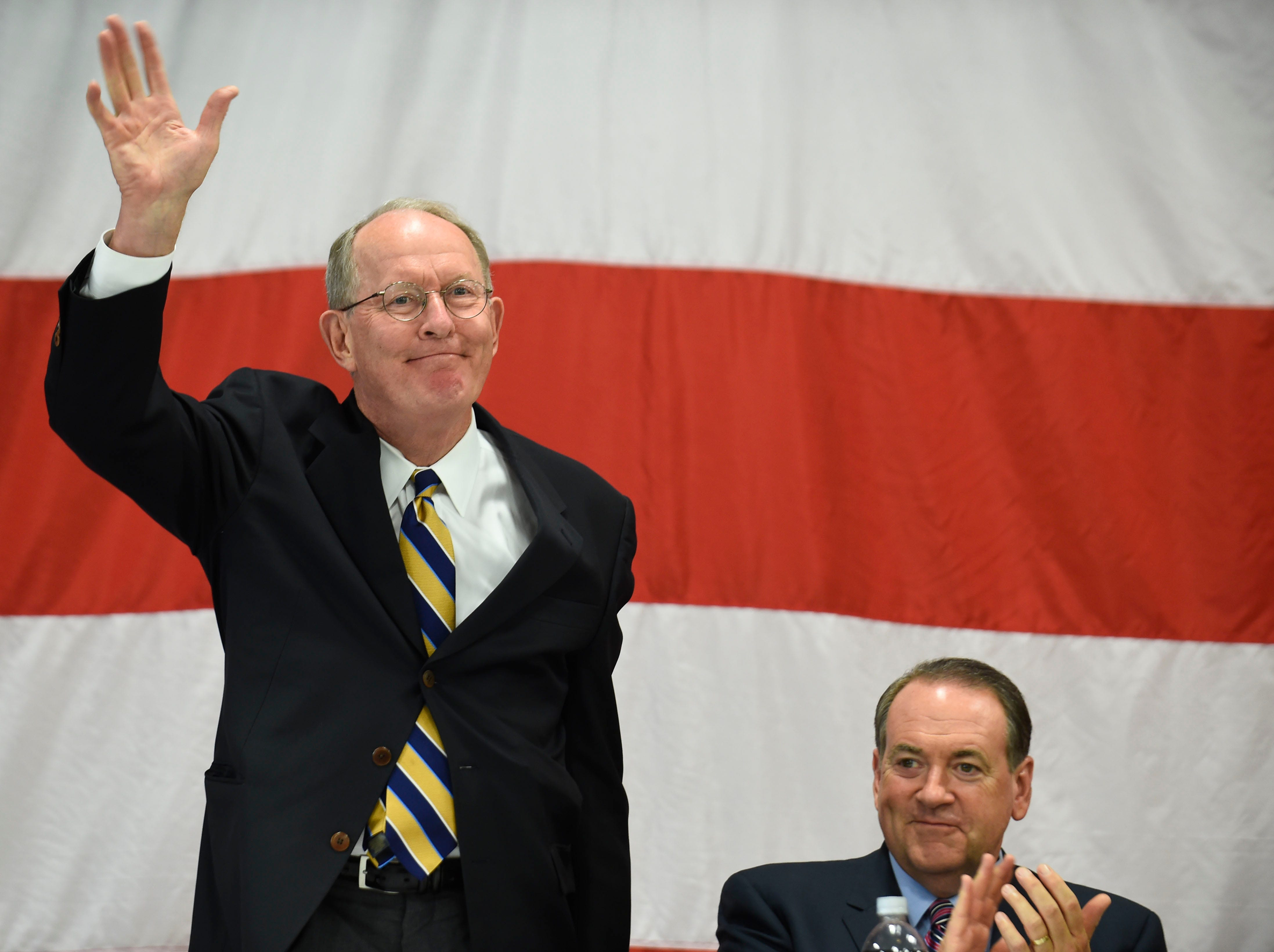 U.S. Sen. Lamar Alexander is introduced during the Lincoln Reagan Dinner at Campbell County High School in LaFollette, Saturday, July 12, 2014. Seated beside is former Arkansas Gov. Mike Huckabee.