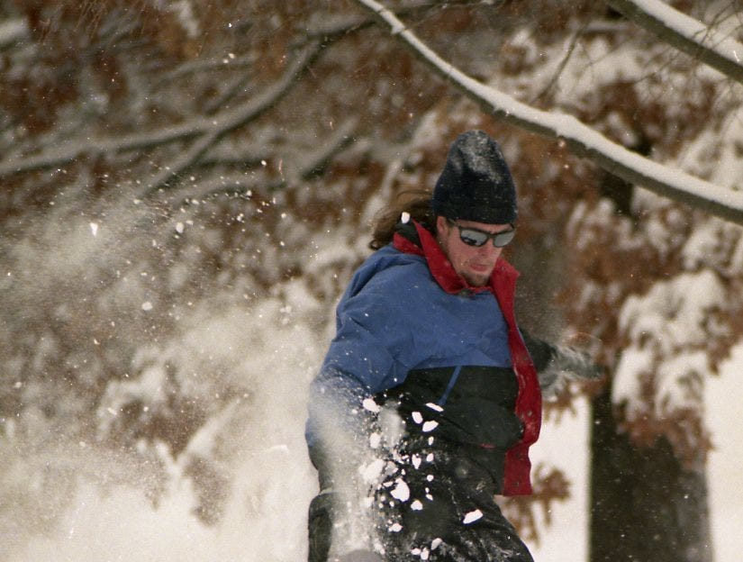 UT student Nate Holder enjoys the sharp drop-off around Ayres Hall on UT's campus in January 1996. Holder and many of his friends got a chance to snowboard on the freshly fallen snow.
