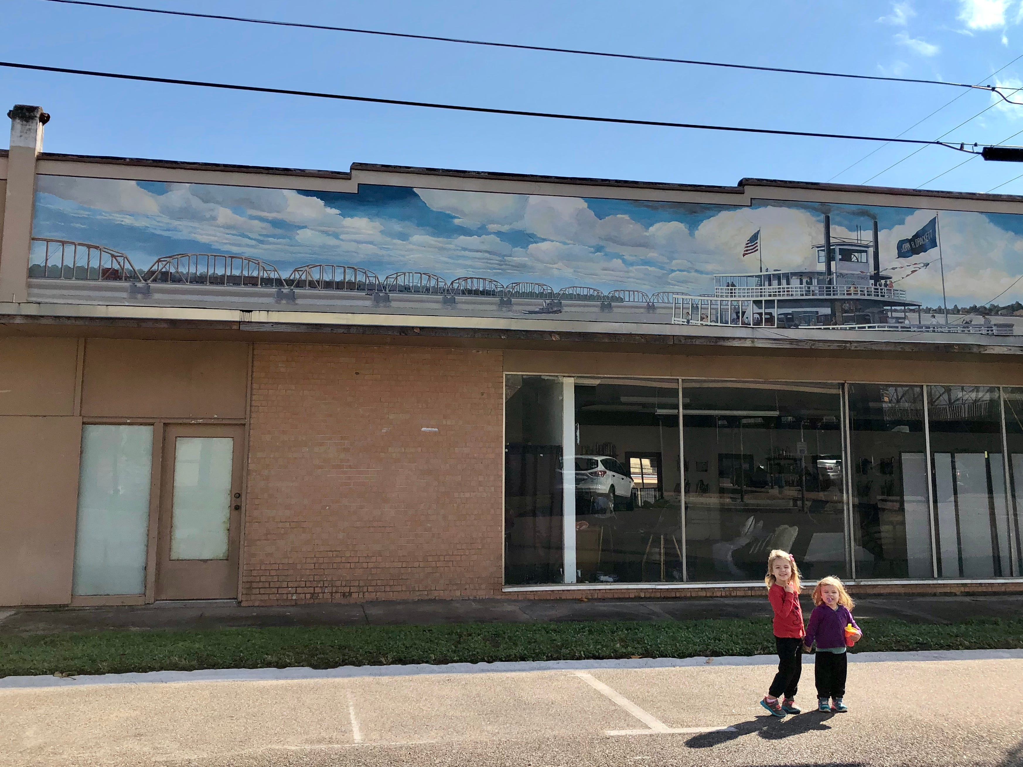 Avery and Marie Guidry pose for a photo in front of a mural in historic downtown Morgan City as their family tours the Bayou Teche Byway.