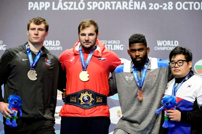 From left, Fowlerville graduate and silver medalist Adam Coon stands on the podium at the World Wrestling Championships with gold medalist Sergey Semenov of Russia, and bronze medalists Oscar Pino Hinds of Cuba and Minseok Kim of South Korea  on Sunday, Oct. 28, 2018.