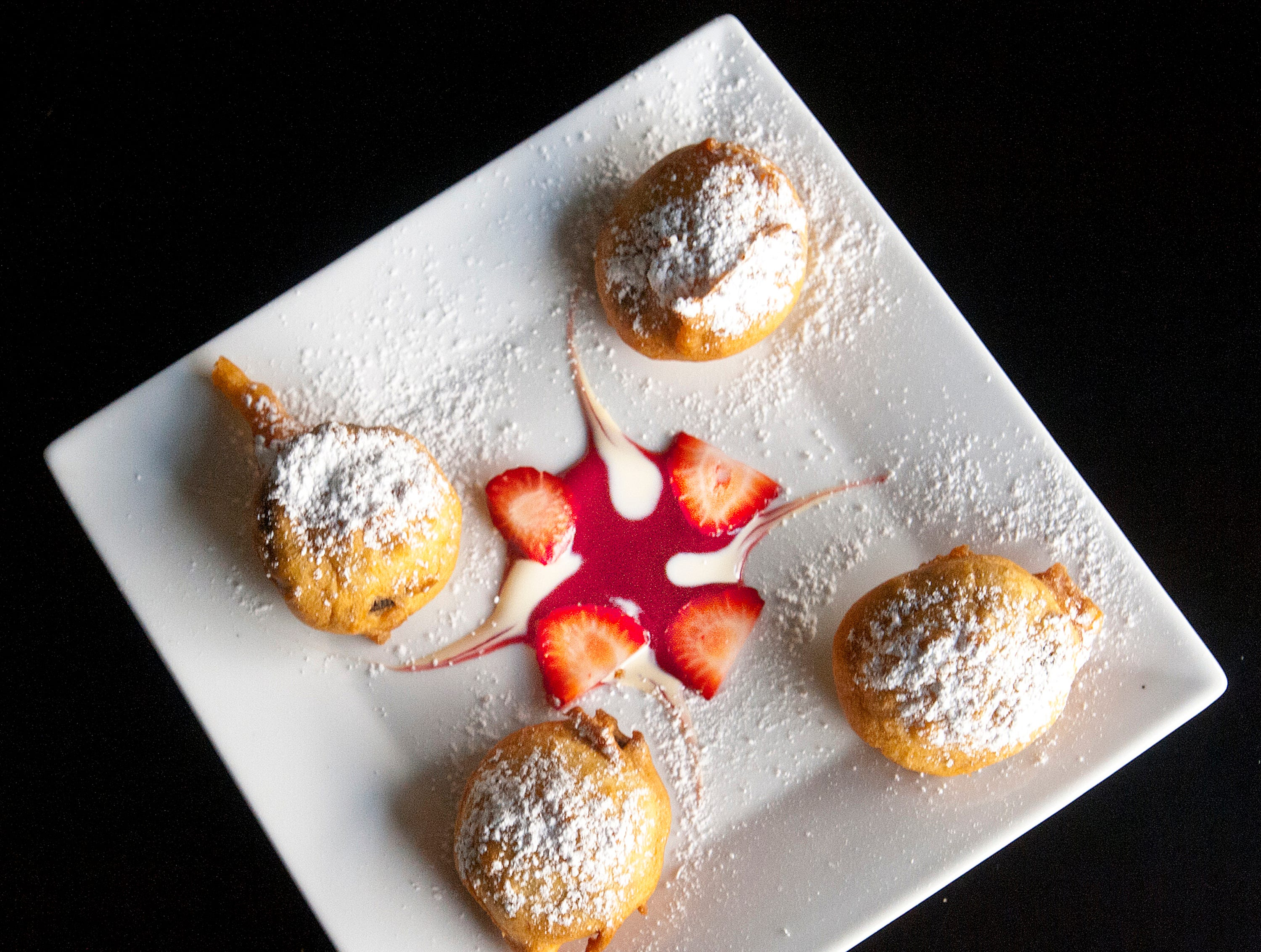 The Flavour Restaurant's beignets are made with a whole Oreo cookie added to a sweet flower batter which is then deep fried and topped with powdered sugar. The dish is seen here with sliced strawberries in raspberry and vanilla bean coulis. The coulis may change seasonally. November 08, 2018