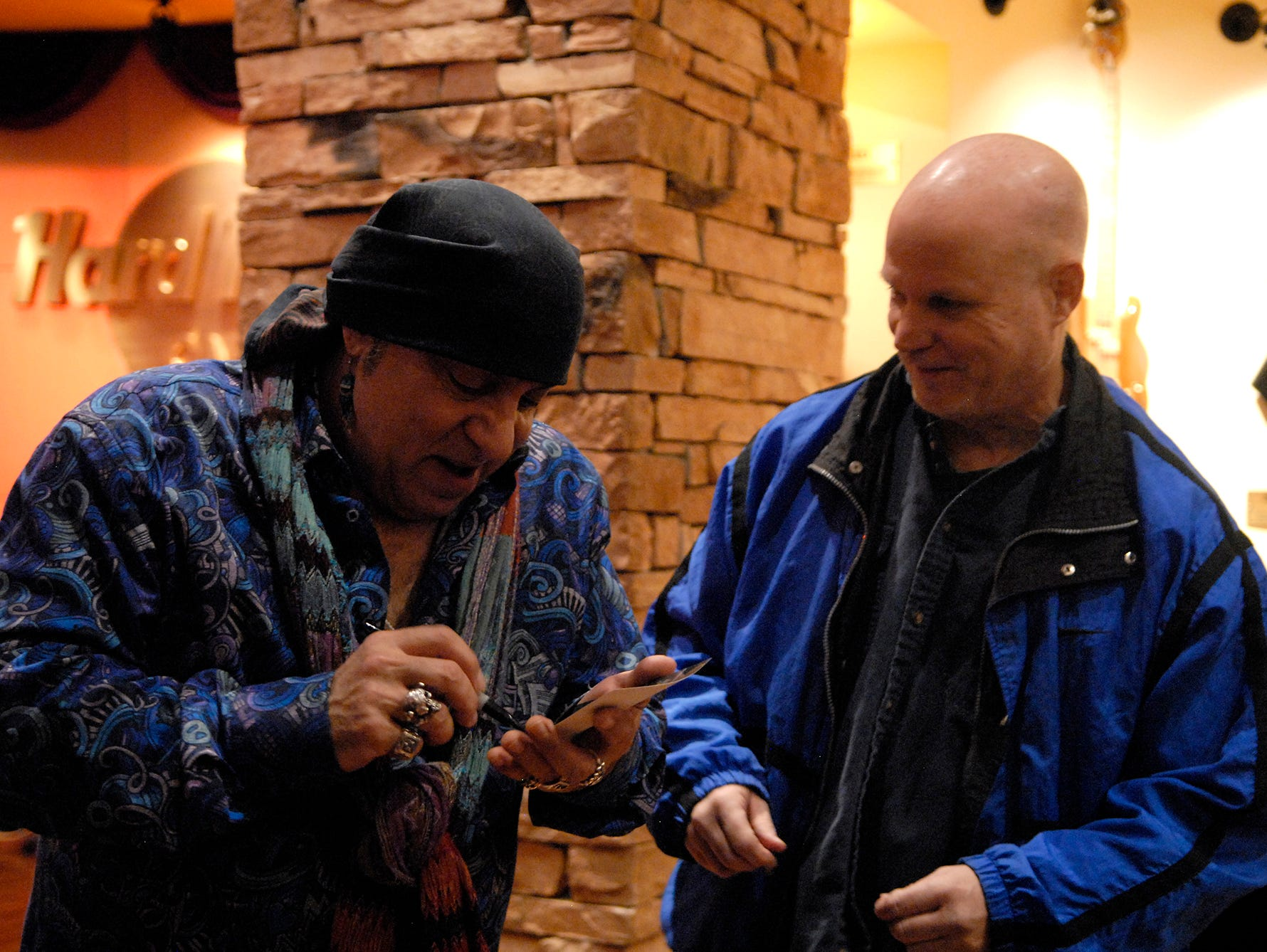 """Steven Van Zandt, of Little Steven and the Disciples and founding member of Bruce Springsteen's E Street Band, signs an autograph for a fan in between playing songs on his radio show """"Little Steven's Underground Garage"""" for Sirius XM Radio at The Hard Rock Cafe on Fourth Street Live!.  July 30, 2018"""