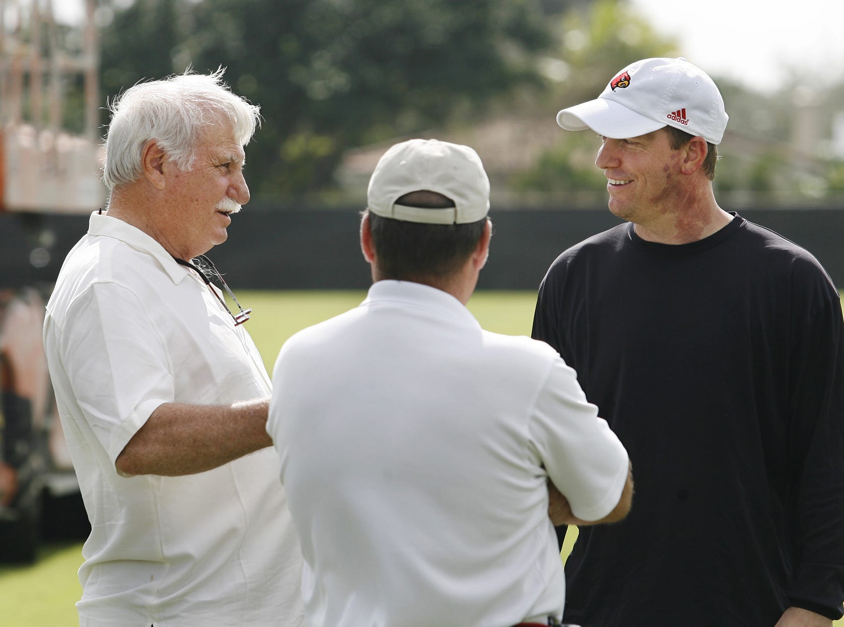 Former UofL head football coach Howard Schnellenberger, left, chatted with his former QB and current UofL QB's coach Jeff Brohm, right, after UofL practiced at the Barry University in Miami Shores, Florida.  Howard's former assistant coach at UofL Kurt VanValkenburgh, center, looked on.  The Cardinals are preparing for their upcoming Orange Bowl appearance on Jan. 2._To go with a Brian Bennett story.