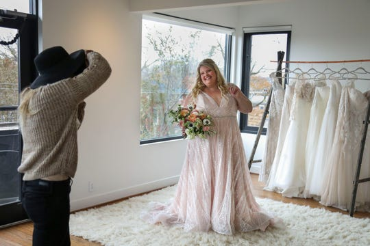 Susan Jordan of Love Hunters photographs Misty Hair, modeling a Couture Closet Bridal dress, in NuLu in Louisville, Ky. on Monday, November 12, 2018. Plus-sizes make up only 16 percent of all apparel sales, though, 67% of women in the United States wear a size 14 or above. Designers are starting to create bridal fashion for size 18 and up in beautiful colors, fabrics, and silhouettes.