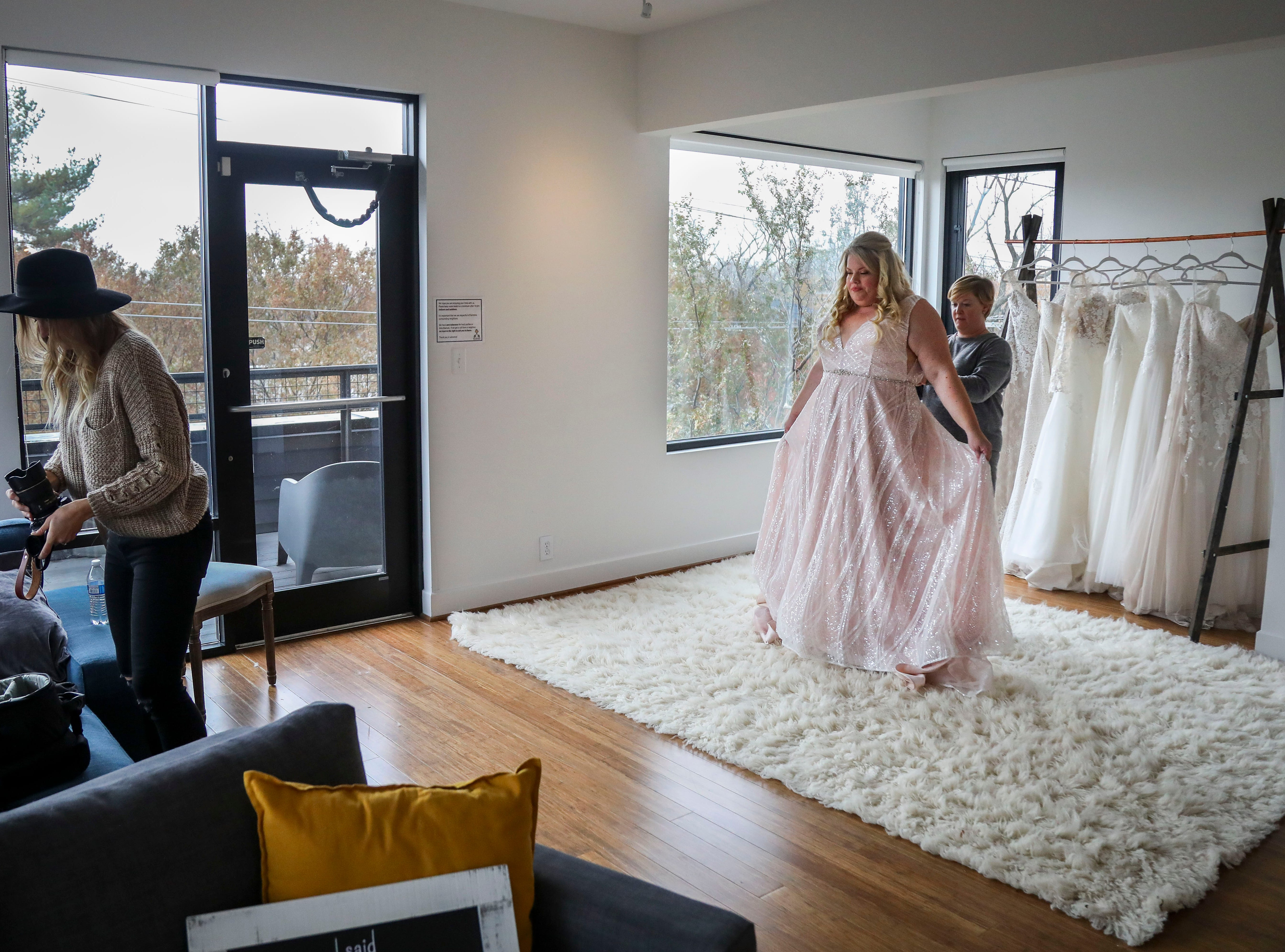 Co-owner of Couture Closet Bridal adjusts Misty Hair's dress while photographer Susan Jordan of Love Hunters switches lenses NuLu in Louisville, Ky. on Monday, November 12, 2018. Plus-sizes make up only 16 percent of all apparel sales, though, 67% of women in the United States wear a size 14 or above. 