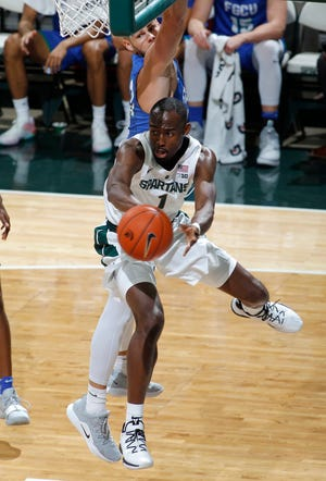 Michigan State's Joshua Langford dishes off under the basket against Florida Gulf Coast's Brady Ernst, rear, during the first half Sunday night in East Lansing.