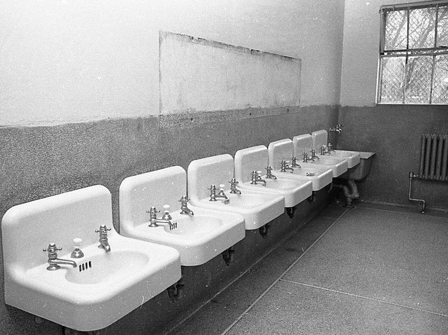 This 1968 photo shows a bathroom in one of the campus buildings at the Boys Training School in Lansing. The bathroom in this detention cottage did not have a mirror due to damage in a fight. Established in 1856, the school served as a reform school for boys until it closed in 1972.