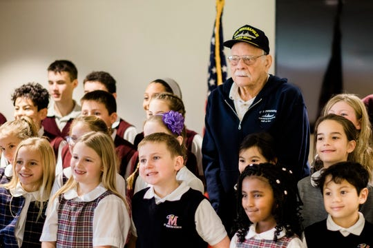 World War II veteran Dick Thelen, 91, poses with students from St. Martha's School in Okemos, Michigan.