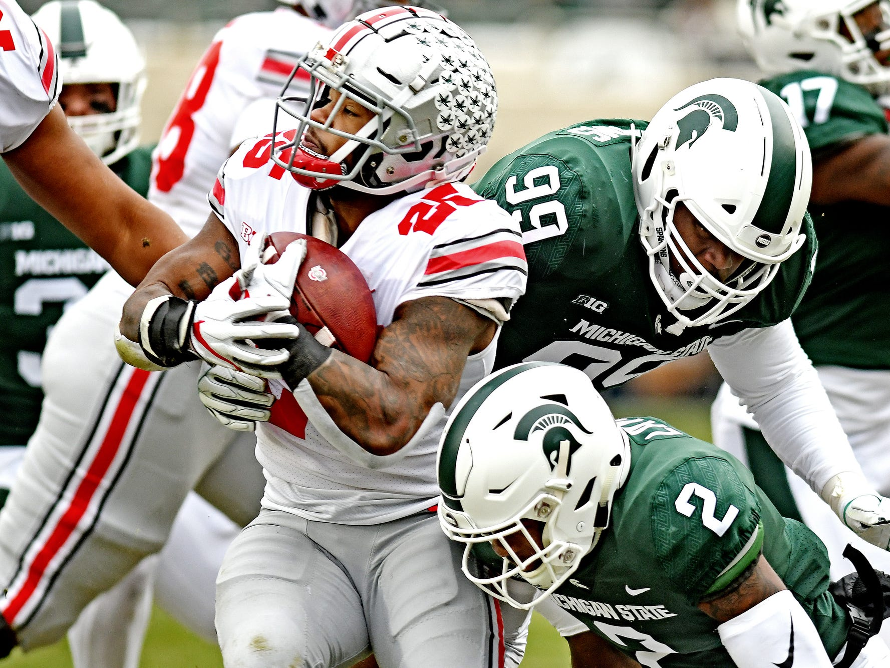 Michigan State's Raequan Williams, right, and Justin Layne, bottom, tackle Ohio State's Mike Weber Jr. during the first quarter on Saturday, Nov. 10, 2018, in East Lansing.
