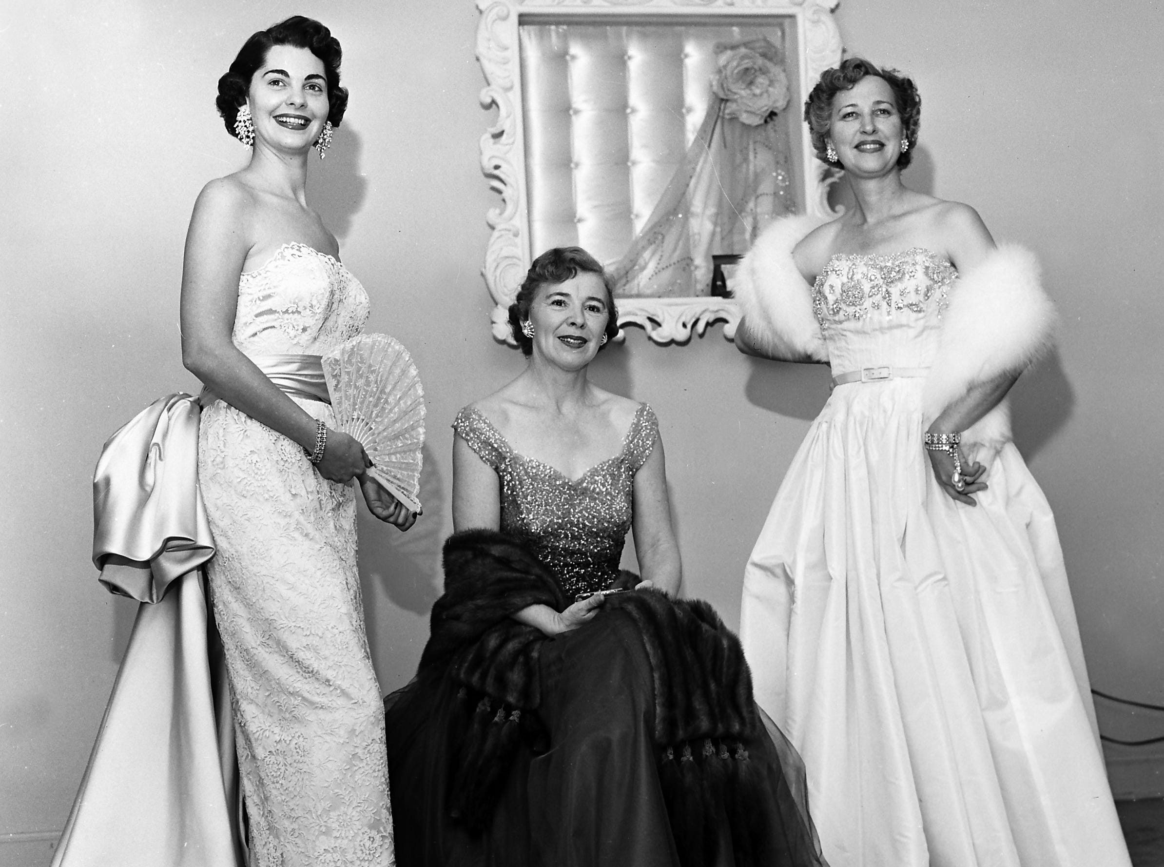 Showing a few of the new winter fashions that will be modeled at the Duration Club's annual Stars and Stripes Ball in November 1952 are (Left to Right) Mrs. Dabney Crump Jr., Mrs. Charles A. Harrelson and Mrs. John Davis Hughes.  Mrs. Crump's lace sheath gown features a wide satin train draped from the waistline, and Mrs. Harrelson's gown, styled with a fitted bodice embroidered in rhinestones and a bouffant tulle skirt shading from violet to royal purple, is accented by a lovely mink stole.  Mrs. Hughes wears a white tissue taffeta strapless gown with the bodice etched in pearls and rhinestones.  The fashion show will be staged by LaClede's.