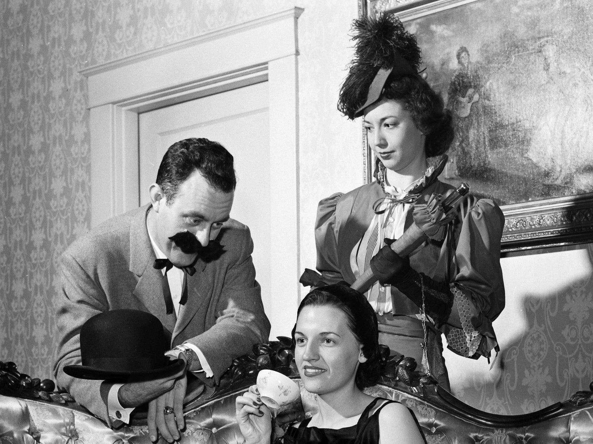 "Getting in the mood for ""A Night at the Flickers"" in Nov 1951 are Charles Ellis Jr., Miss Halcyon Hughes (Seated) and Mrs. Thomas L. Summers.  The three, all members of the Young Artist Group of the Beethoven Club, will appear in costume when the group presents an evening of silent movies and Gay Nineties musical numbers at Grace-St. Luke's Parish House."