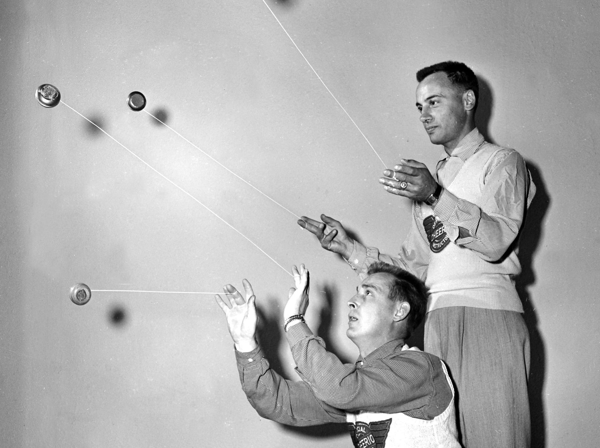 "Mac Culhane (crouching) and Al Gallo, young yo-yo artists from Toronto, demonstrate method of operating four yo-yos at once in November 1951.  This production number, a variant of one named ""Fireworks,"" is too technical to teach Memphis youngsters, who must be content with ""Walk the Baby,"" ""Eat Spaghetti,"" and similar horrors."