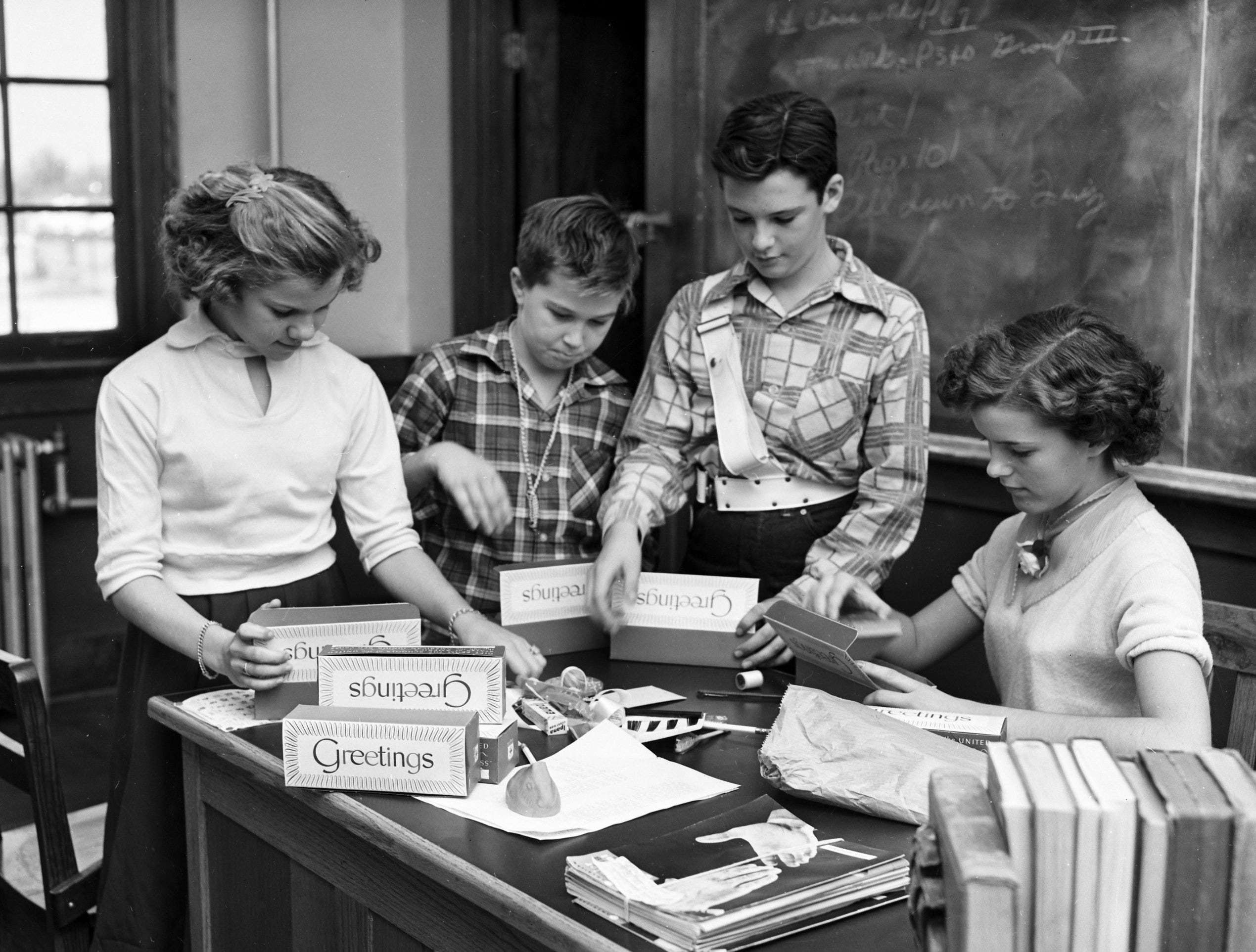 Boys and girls all over Memphis and the Mid-South are busy in November 1952, filling Junior Red Cross gift boxes which soon will be sent to needy students in distant lands.  Active in the gift box campaign at Treadwell are these four, who spent their afternoons packing the boxes with articles they'd bought.  Busy at work are (From Left) Loretta Lewter, 12, of 769 Freeman; Alna Bonds, 11, of 3697 Vernon; Lewis Gross, 13, of 1053 Gordon and Margaret Barrow, 13 of 3458 Bowen.