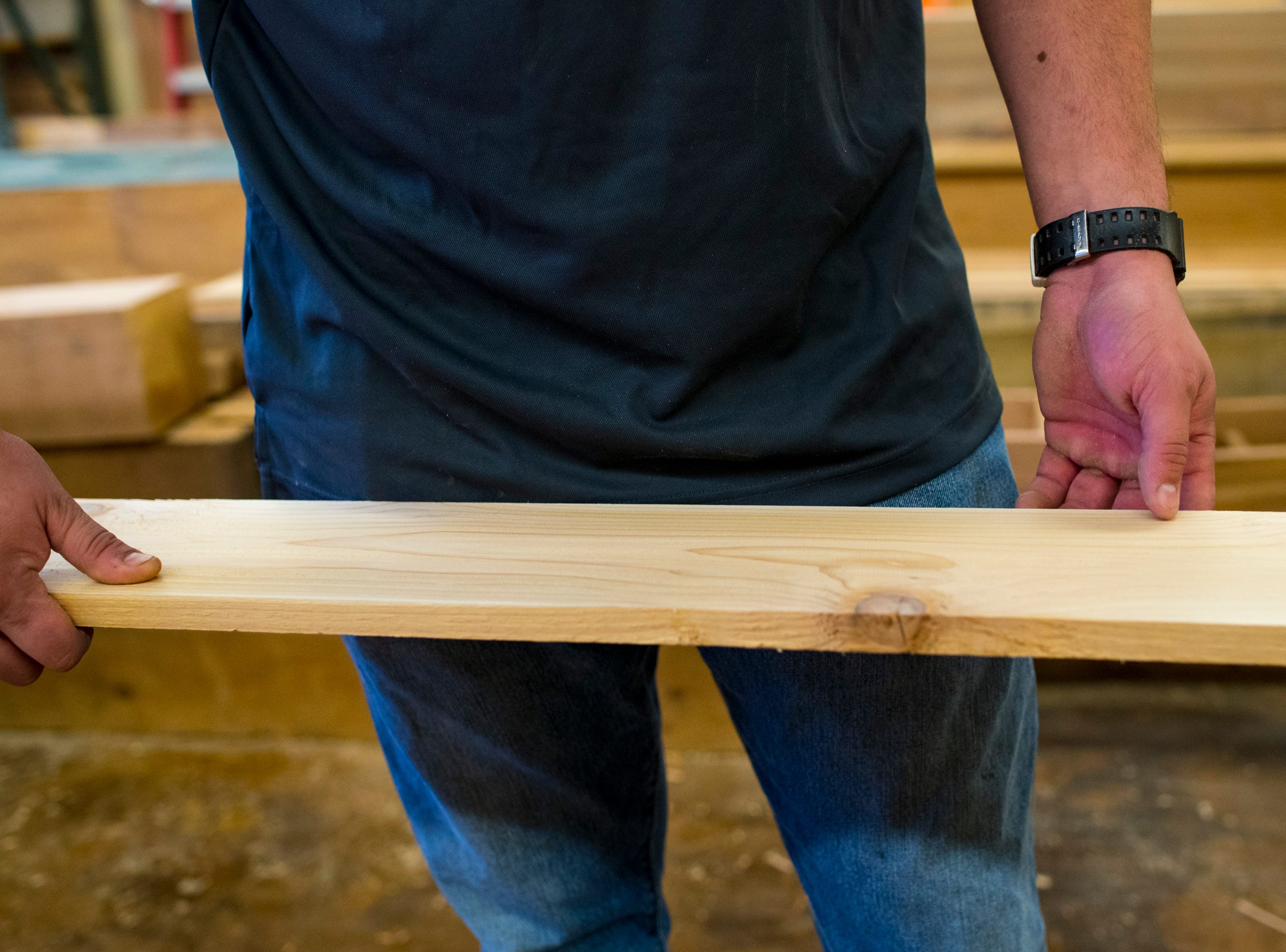 Colin Hemberg holds a board coming out of a planer at TN Box Beams in Franklin on Friday, Nov. 9, 2018. TN Box Beams will be featured on the HGTV show Property Brothers Buying + Selling on Nov. 14.