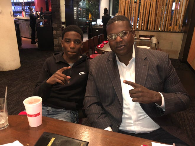 Alfred Washington sits with his little brother, Justin, at a restaurant