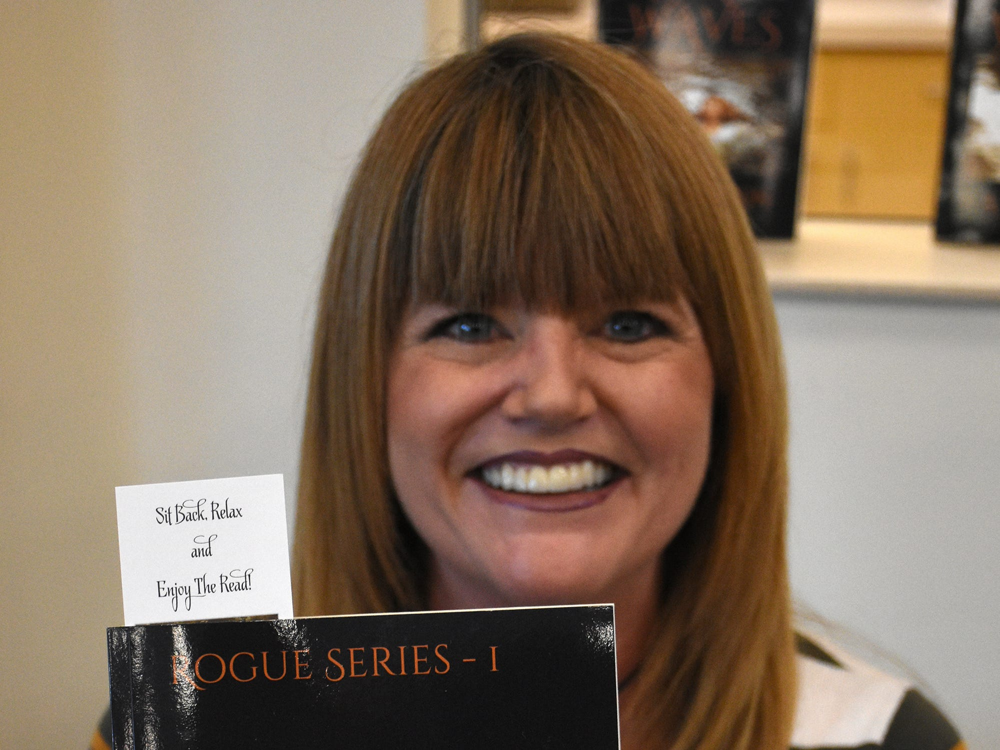 "Janice Ann Anderson with her novel ""Rogue Waves."" The Collier County public library system hosted an author fair at the South Regional library branch, with nearly four dozen local writers and talks from two eminent authors."