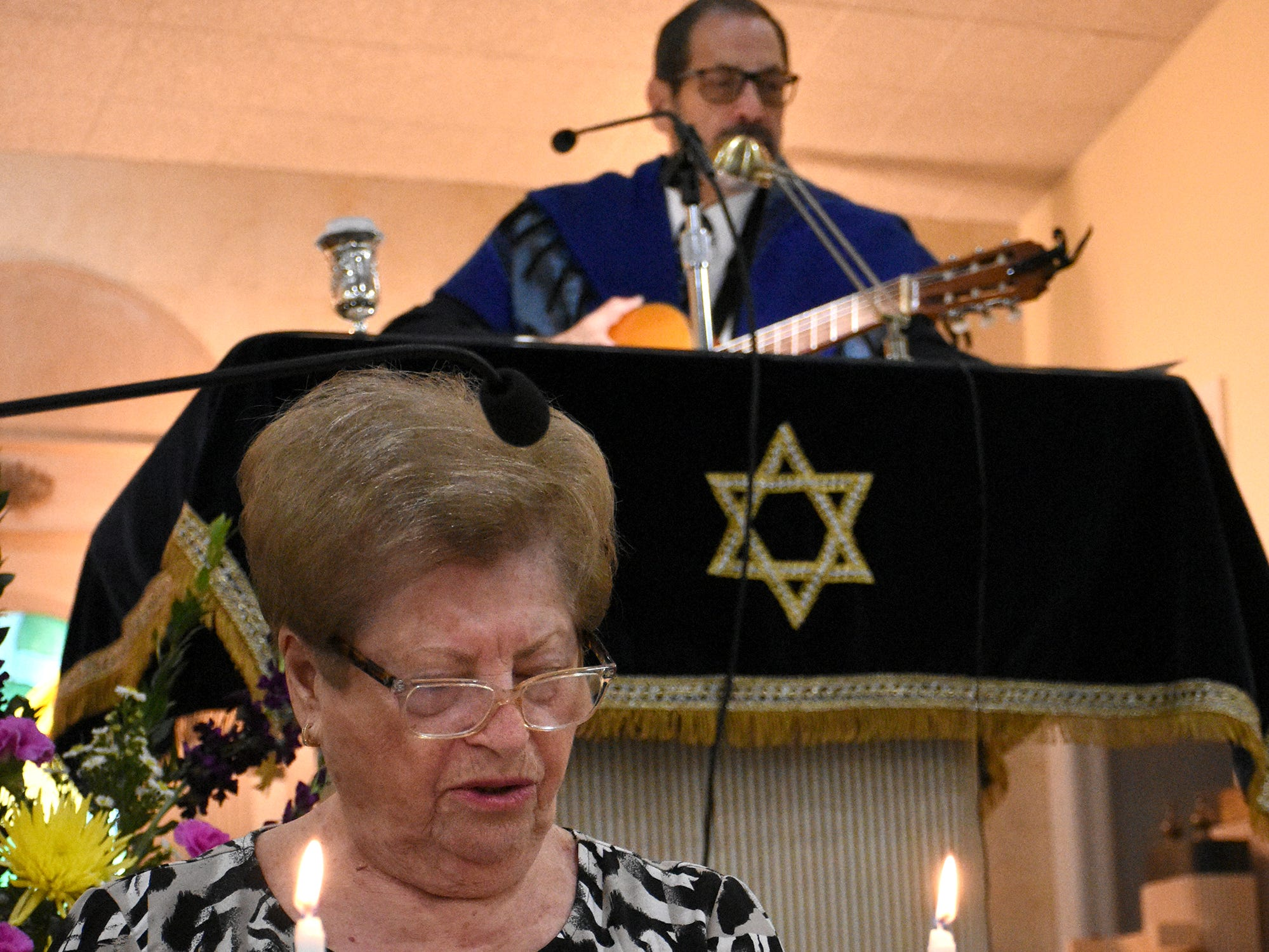 Eta Gluzband reads a prayer with help from Rabbi Mark Gross. The Jewish Congregation of Marco Island held a Shabbat service Friday evening marking the 80th anniversary of Kristallnacht, when Nazi Germany brought perseution of Jews out into the open.