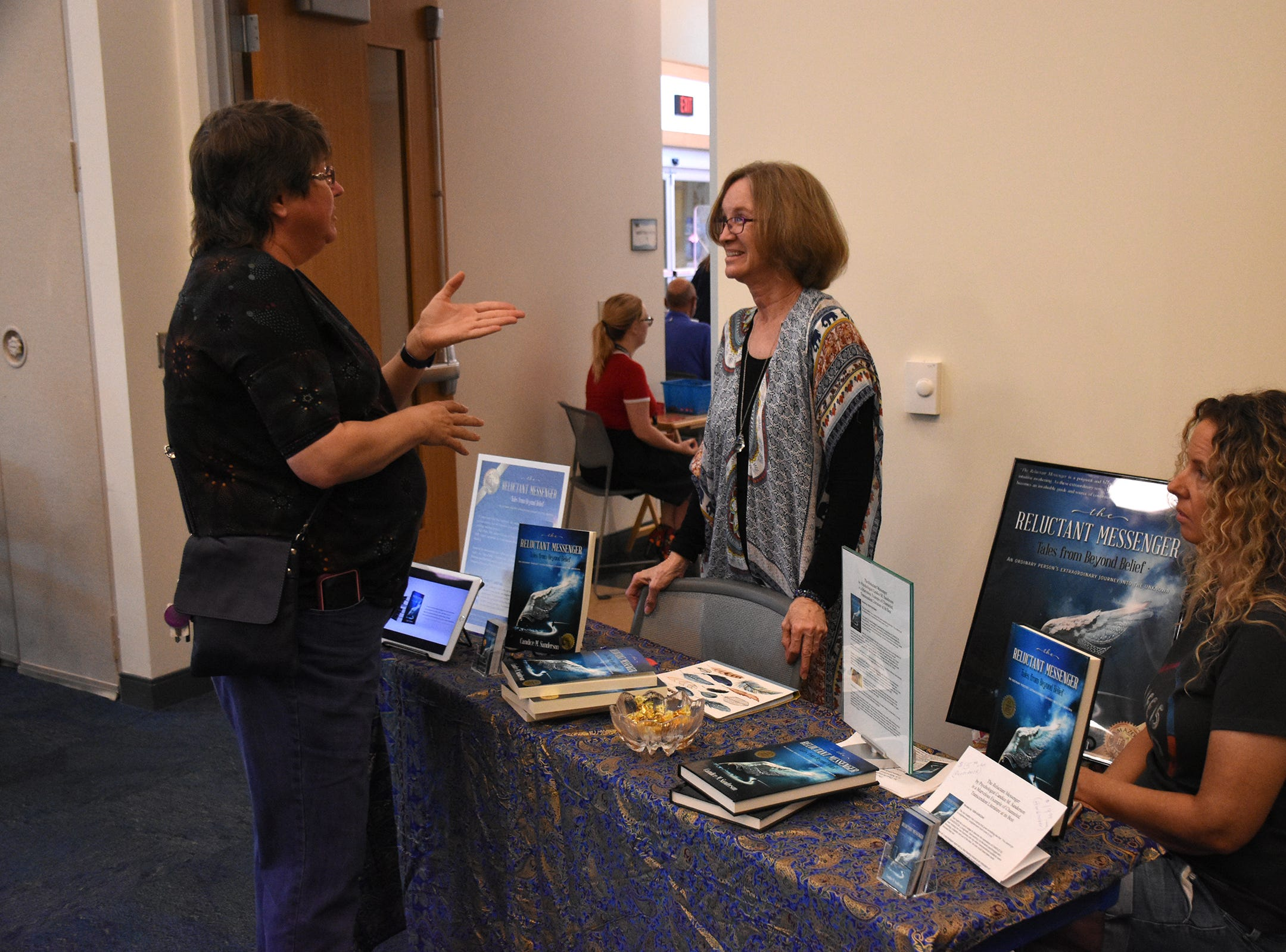 Author Candice Sanderson, center, speaks with Connie Bettinger. The Collier County public library system hosted an author fair Nov. 10 at the South Regional library branch, with nearly four dozen local writers and talks from two eminent authors.