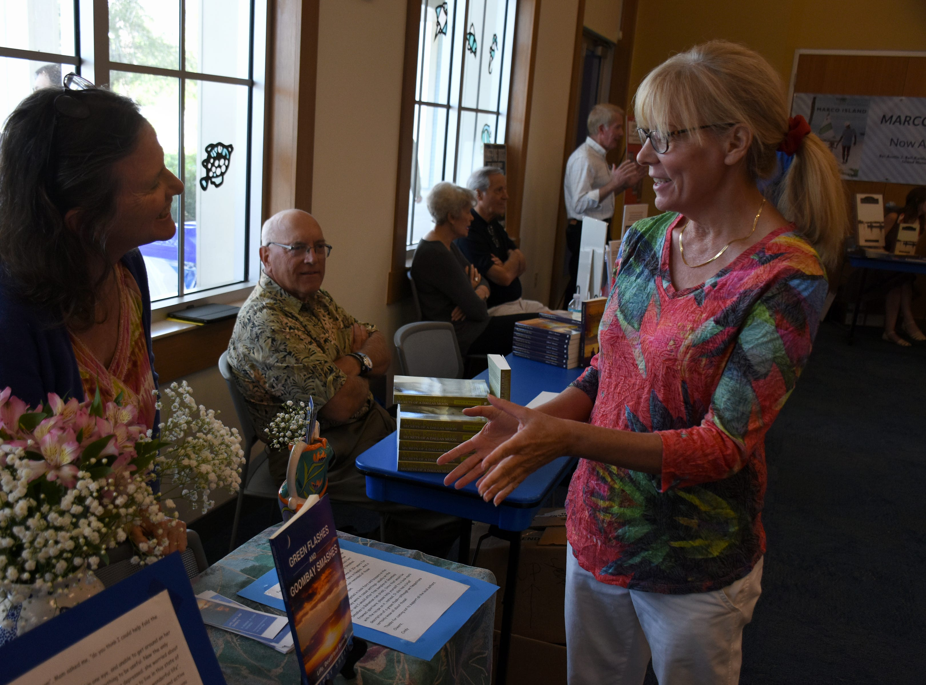 Author Cindy Shearer, left, talks with Janice Gilbert. The Collier County public library system hosted an author fair Saturday at the South Regional library branch, with nearly four dozen local writers and talks from two eminent authors.