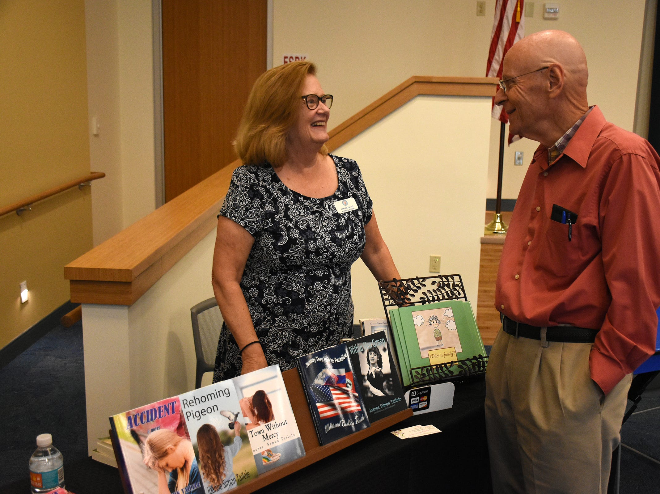 "Joanne Simon Tailele, who writes ""dark women's fiction"" plus children's books, talks with Ed Miller. The Collier County public library system hosted an author fair Nov. 10 at the South Regional library branch, with nearly four dozen local writers and talks from two eminent authors."