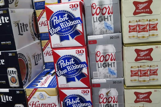 In this photo taken on Thursday, Nov. 8, 2018, cases of Pabst Blue Ribbon and Coors Light are stacked next to each other in a Milwaukee liquor store. Pabst Brewing Company and MillerCoors are heading to trial starting Monday, Nov. 12, to settle a contract dispute in which Pabst accuses the brewing giant of trying to undermine its competitor by breaking a contract to make their products. (AP Photo/Ivan Moreno) ORG XMIT: RPIM201