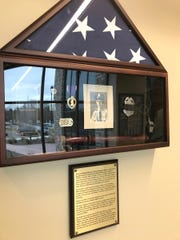A shadowbox at the Baraboo police station shows the photo, Purple Heart and dogtags of police officer Robert Marquardt who enlisted in the Army during World War II and was killed by a German sniper while battling for to liberate a city in France in 1944.