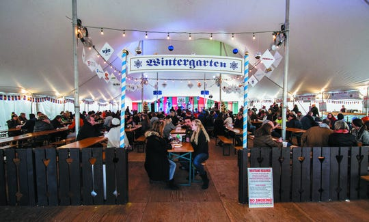 Visitors enjoy delicious food and drink in the Wintergarten tent at The German Christmas Market in Oconomowoc.