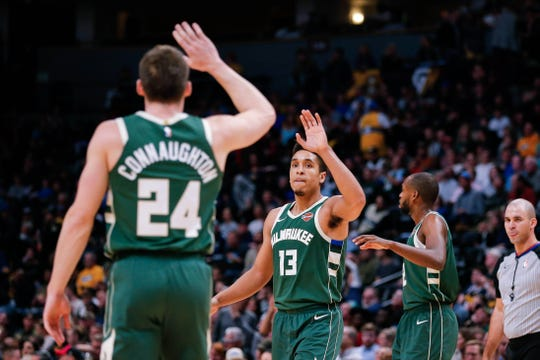 Malcolm Brogdon (13) celebrates with guard Pat Connaughton.