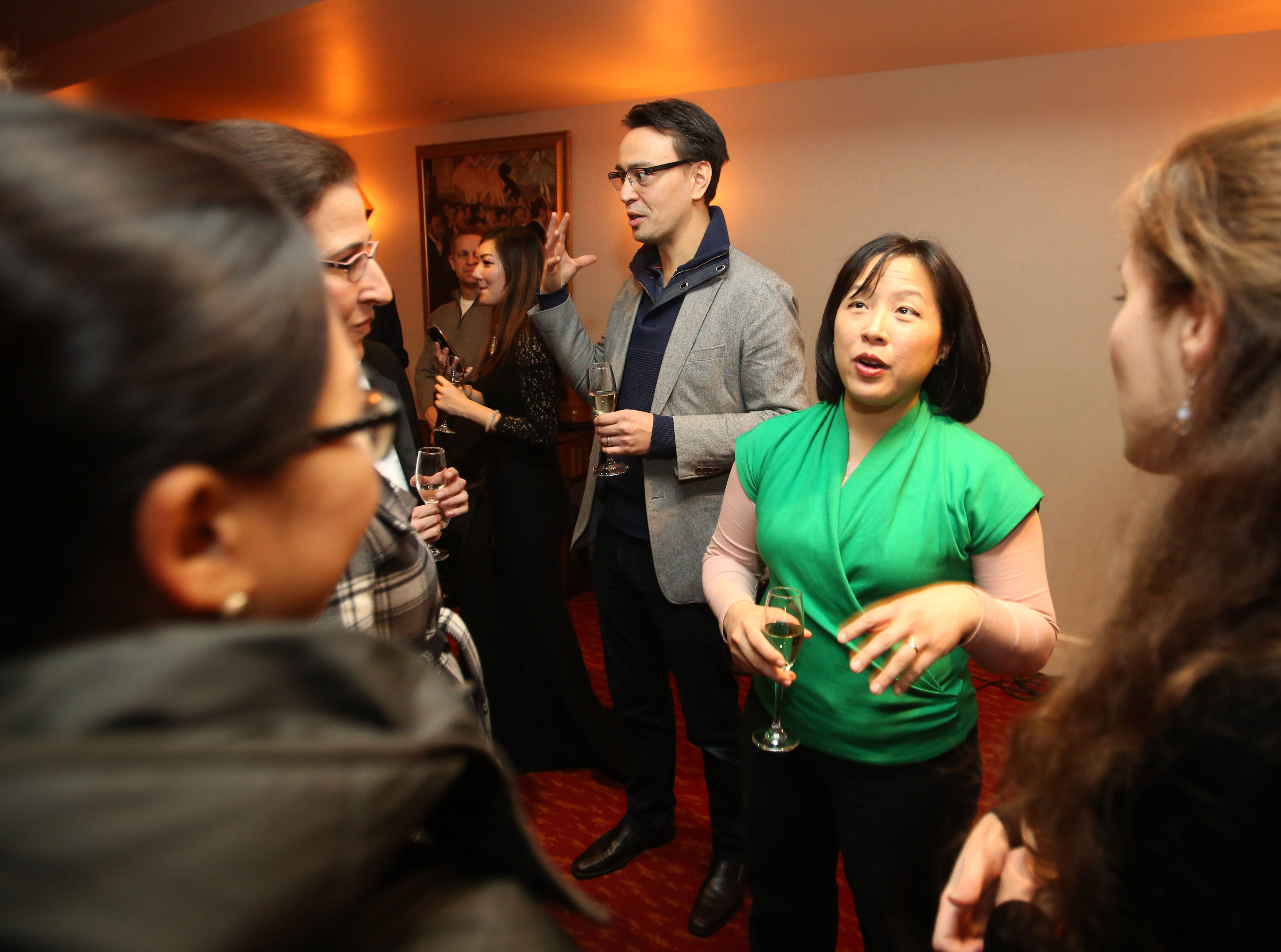 Ken-David Masur (back center) and spouse Melinda Lee Masur (in green) greet Milwaukee Symphony musicians during an event introducing him as the orchestra's next music director.