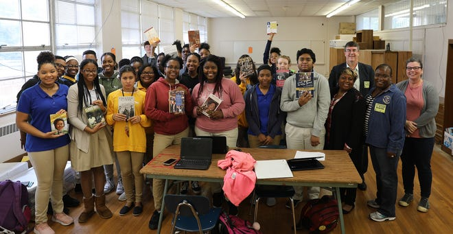 Students at Booker T. Washington Magnet High School receive some of the books donated by the Muir S. Fairchild Research Information Center. On right, Air University library staff Ataya Wallace, Mehmed Ali, Monica Tolver with media specialist Jennifer Sanford.
