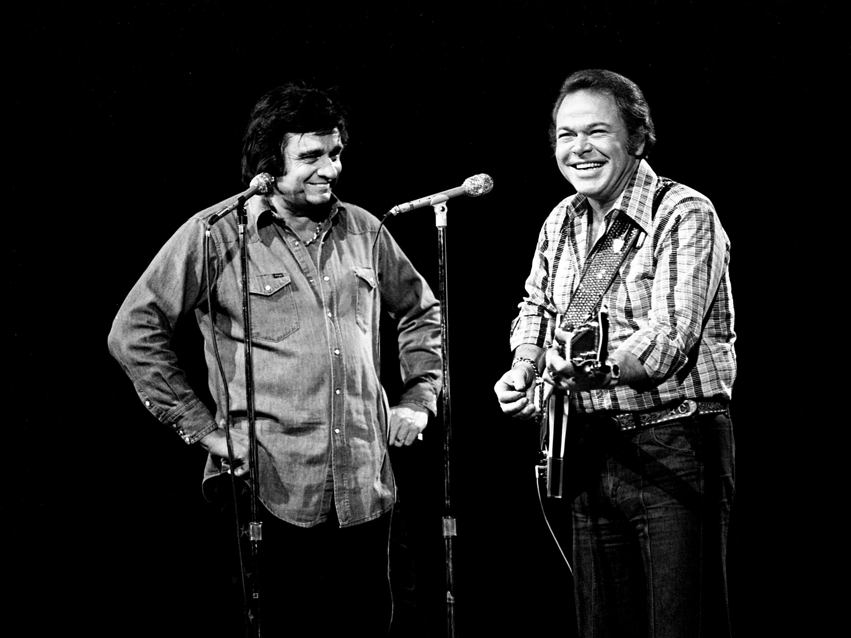 "Johnny Cash, left, and host Roy Clark enjoy a little lighthearted clowning on the Grand Ole Opry House stage during the afternoon's rehearsal for the three-hour NBC ""Big Event"" television special, ""Fifty Years of Country Music,"" on Jan. 4, 1978."