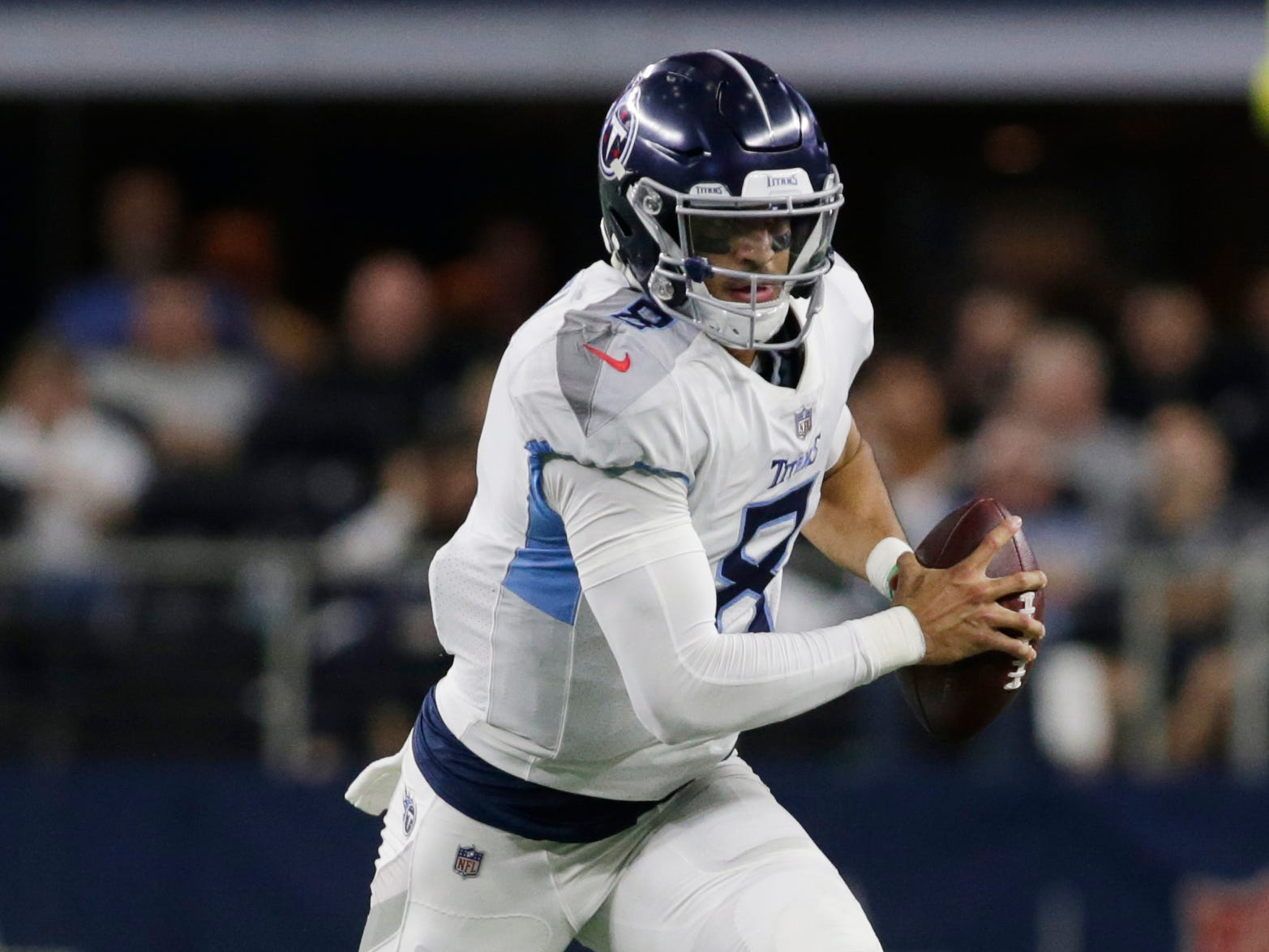 Tennessee Titans quarterback Marcus Mariota (8) scrambles in the third quarter against the Dallas Cowboys at AT&T Stadium.