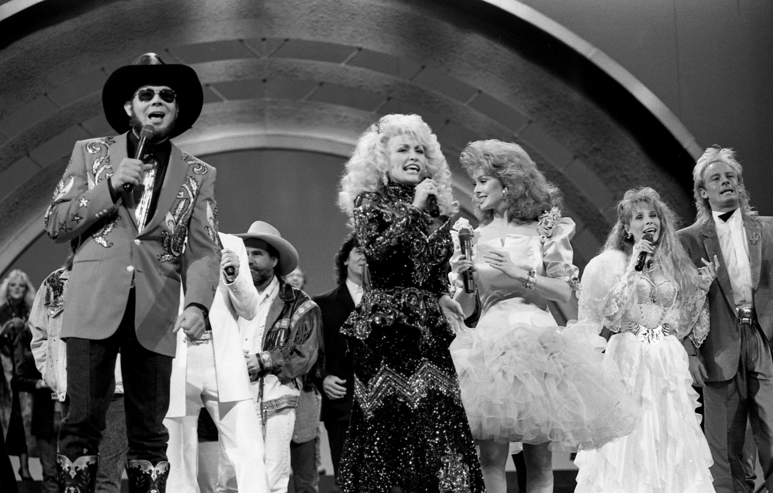 Host Dolly Parton sings with other county-music stars in the opening number of the CMA Awards show at the Grand Ole Opry House in 1988.